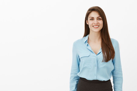 Portrait of happy outgoing european female entrepreneur in blue blouse and black skirt, smiling broadly and gazing at camera, being ready to help or give advice, standing carefree over grey wall
