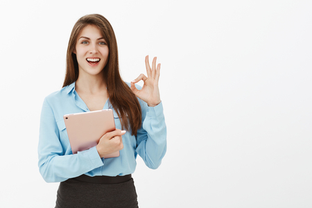 Great opportunities for young employees. Pleased charming european female in blue blouse, raising hand with ok or okay gesture, holding pink digital tablet, smiling broadly and being satisfied Stock Photo