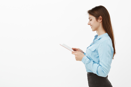 Studio shot of charming carefree businesswoman in blue blouse and black skirt, standing in profile over grey wall, holding digital smartphone, gazing with satisfied happy smile at screen of gadget
