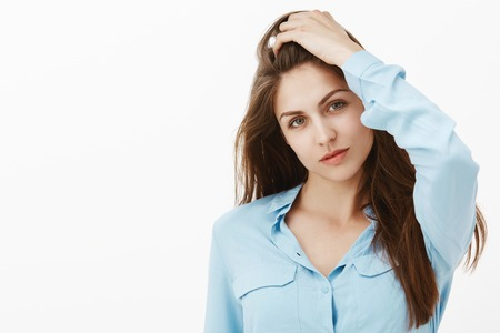 Indoor shot of attractive hot european girlfriend in blue blouse, touching hair with raised hand and gazing at camera with confident flirty expression, feeling self-assured and beautiful