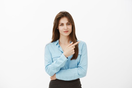 Try to find answer in that direction. Portrait of confident charming brunette female coworker in blue blouse, pointing at upper right corner with index finger and smiling, being assured she is right