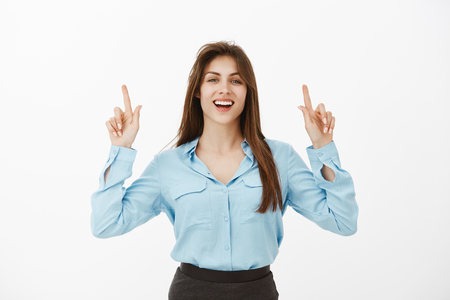 Portrait of emotive charming brunette in blue blouse, raising index fingers and pointing upwards, looking at camera with broad smile and self-assured expression, being proud and confident