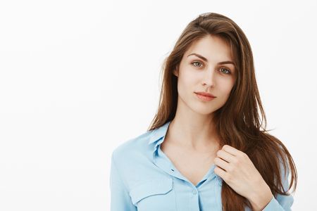 Good-looking seductive european girlfriend in blue blouse, gently touching collar, tilting head and smiling flirty at camera, being relaxed and romantic, standing tender over gray background Stock Photo