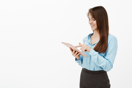 Let me check my schedule before planning. Portrait of pleased carefree attractive woman with brown hair, typing in digital tablet and smiling broadly at screen, messaging or sending photo to friend Stock Photo
