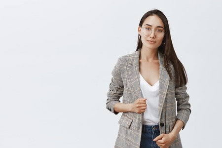 Confident and successful female lawyer ready help solve any problem. Portrait of stylish feminine woman in trendy jacket and glasses, smiling politely at camera and standing over gray background Stock Photo