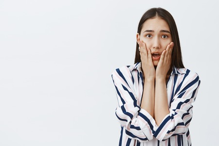 Friend told shocking news. Portrait of stunned and intense good-looking female student in striped blouse, gasping, holding palms on cheeks while sympathizing heartbreaking story, posing over gray wall Stock Photo