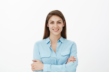 Girl determind be productive today. Confident happy brunette female with bright smile holding hands crossed on chest while standing in blue blouse and grinning, knowing how to deal with deadlines