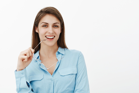Excited charming brunette female student in blue blouse, biting rim of glasses and smiling broadly, being in great mood while creating new concept, having great plan or interesting intension