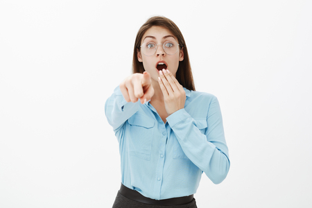 Look there, it is unbelievable. Shocked excited funny woman in glasses and blue blouse, covering opened mouth with hand while dropping jaw and pointing at camera, being amazed and impressed Stock Photo