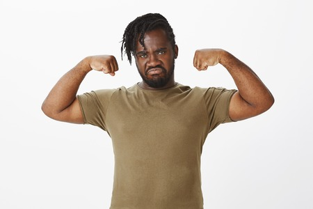 Portrait of serious-looking masculine dark-skinned plump guy in military clothes, raising hands and showing biceps, frowning, grimacing with threatening expression, standing over gray wall Stock Photo