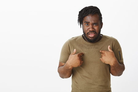 Guy shocked friend blames him. Frustrated questioned young african-american man in military outfit, pointing at chest, staring surprised at camera, lifting eyebrow with doubt, standing over gray wall Stock Photo
