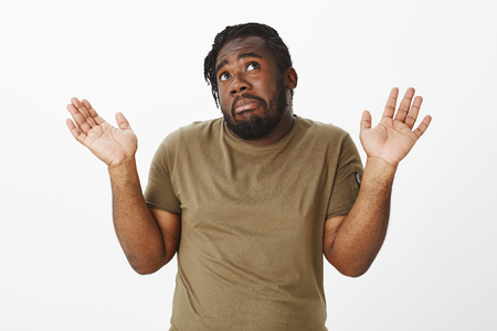Unaware funny dark-skinned man with beard, looking up with unsure expression, lifting palms cluelessly, being indifferent and careless, having no idea or clue what happening, staying out of problems