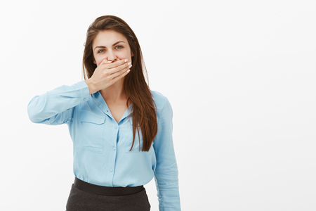 Woman needs keep mouth shut. Portrait of casual european female brunette in blue blouse, covering mouth with palm and staring at camera, keeping secret or being offended, not talking to boyfriend Stock Photo