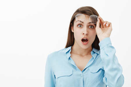 No way, what happened. Portrait of shocked emotive adult female brunette, taking off glasses, gasping and dropping jaw, lifting eyebrows from surprise and amazement, standing stunned over grey wall