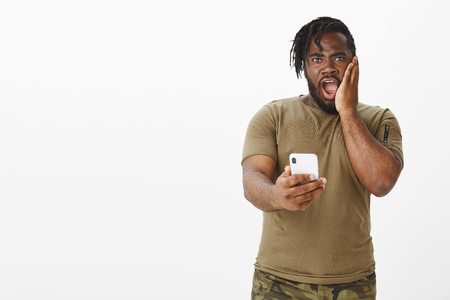 Portrait of shocked surprised attractive dark-skinned guy with beard in military t-shirt and pants, dropping jaw, holding smartphone, being amazed with received message, staring stunned at camera