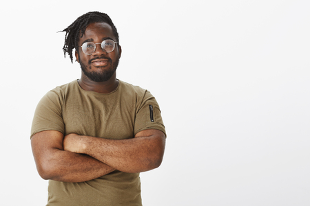 Smart happy and confident african-american in stylish transparent glasses, holding hands crossed, standing in self-assured pose, smiling broadly at camera, posing for advertisement over grey wall