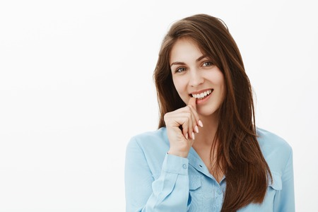 Flirty charming female employee in blue blouse, smiling broadly and biting thumb while gazing at camera with intrigued and interested expression, having great idea or intention over gray wall