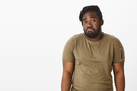 Waist-up shot of gloomy unaware dark-skinned man with beard, shrugging and pulling lips down, being unhappy and confused, standing clueless over gray background, having no idea about topic Stock Photo
