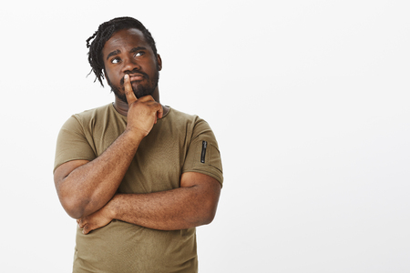 Studio shot of curious dark-skinned ordinary guy with beard in olive t-shirt, looking up and holding finger on lip while thinking, making decision or choice, standing thoughtful over grey background