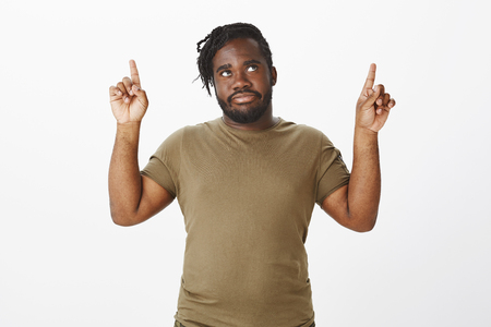 Portrait of bothered displeased african bearded man in military clothes, raising index fingers, looking and pointing up with annoyed expression, being disturbed with loud noise from neighbours