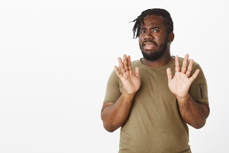 Intense displeased attractive plump guy with dark skin, raising palms in surrender, showing unwillingness to participate in event, rejecting offer or being disgusted with something over gray wall