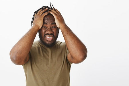 What can I do, help. Anxious devestated african american in military t-shirt, holding hands on head and clenching teeth from nervous feelings, Miserable and unaware how solve problem, stuck with issue Stock Photo