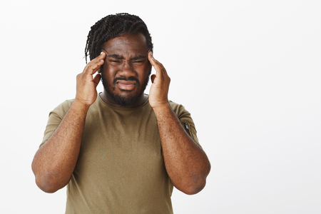 Cannot concentrate from headache. Portrait of bothered gloomy dark-skinned guy in military t-shirt, frowning and grimacing from painful feelings, holding fingers on temples, feeling migraine Stock Photo