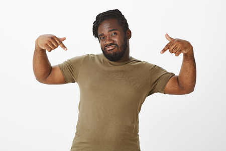 Look how cool I am. Confident good-looking plump african-american man, making not bad expression, raising index fingers and pointing at chest, talking about himself with self-assured attitude