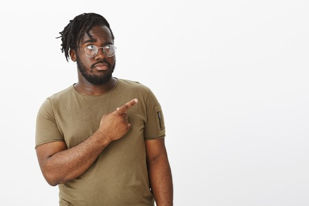 Studio shot of intense suspicious attractive dark-skinned man in casual t-shirt, staring and indicating at upper right corner, being unsure or displeased, standing in doubts over gray background