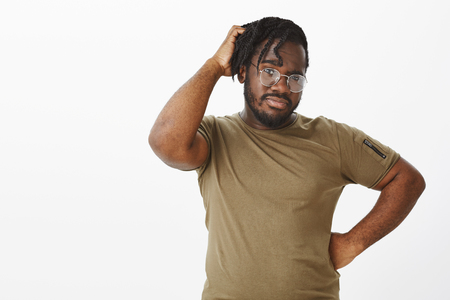 Indoor shot of unsure handsome african american in glasses, holding hand on hip and scratching head, being doubtful while thinking, making choice with confused expression, standing in hesitations