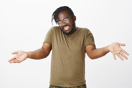 Indoor shot of good-looking careless african-american with beard and trendy haircut, raising palms and shrugging with clueless gesture, being unaware and indifferent, standing happy over gray wall