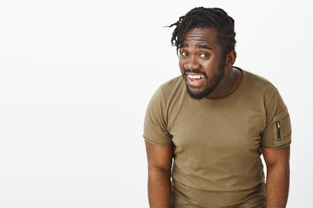 Repeat what you said. Portrait of questioned intense attractive dark-skinned guy in olive t-shirt, bending towards camera while asking question, standing clueless and unaware over grey wall