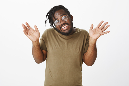 Innoncent careless man having no idea what happened. Portrait of indifferent happy dark-skinned guy in military t-shirt, raising palms in surrender, shrugging and gazing with broad smile right