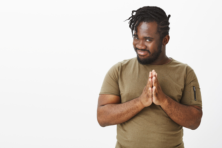 Guy rubbing palms, having nasty evil plan. Intrigued funny african-american man in olive t-shirt, holding hands in pray, tilting head and smiling with curious expression, standing over grey wall
