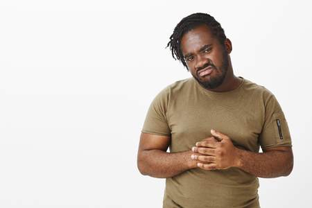 Waist-up shot of displeased gloomy african-american man in military t-shirt, rubbing fingers and staring disappointed at camera, frowning and expressing dislike, looking at something upsetting Stock Photo