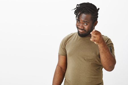 You are out hope. Portrait of confident pleased handsome dark-skinned man in casual outfit, hinting at something while pointing at camera with index finger, smiling curiously over grey wall