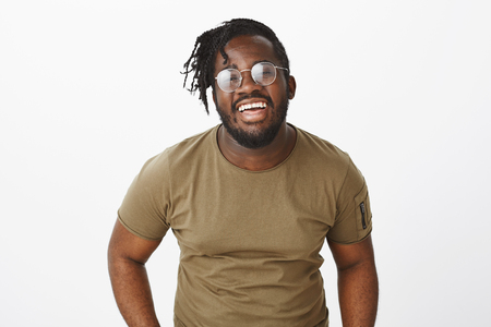 Smile keeps sadness away. Portrait of bright good-looking african american male model in glasses and military t-shirt, laughing out loud and expressing joyful happy attitude over grey wall