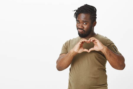Guy always find way to women hearts. Good-looking flirty african-american in military t-shirt, showing heart gesture with hands over chest, folding lips mimicking kiss while confessing in love