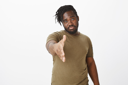 Indoor shot of confident serious-looking african guy with beard, pulling hand towards camera to give handshake, standing self-assured while greeting coworker or friend over greay background