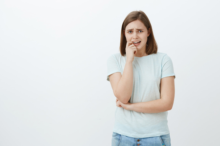 Girl going panic unsure what do. Portrait of anxious timid girlfriend in casual outfit frowning whining and biting fingernail from nervous feelings standing insecure and worried over grey background
