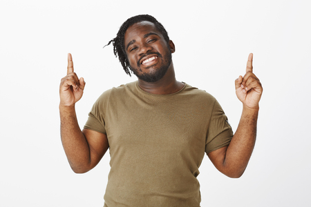 Feeling like winner. Portrait of charming dark-skinned plump man with positive and happy attitude, raising index fingers and pointing up, smiling with satisfied expression, feeling relaxed and pleased