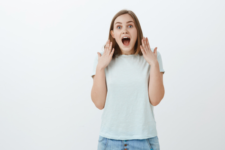 Ear flapps from shocking rumors. Portrait of amazed and excited attractive emotive woman in cute t-shirt shaking palms near head opening mouth staring surprised at camera hearing incredible good news