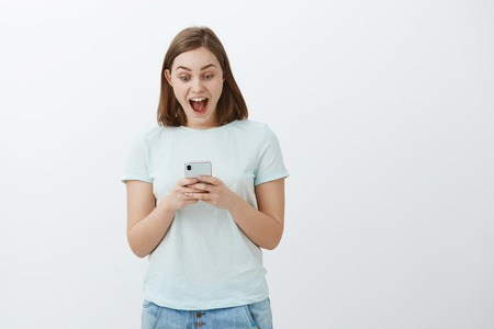 Woman amazed like on heaven from received message. Enthusiastic cute girl in t-shirt smiling rejoicing, triumphing from good news reading interesting article in smartphone gazing at cellphone screen