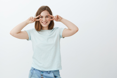 Girl enjoying youth. Charming friendly-looking young european female in casual t-shirt showing peace or disco gestures over eyes feeling playful and entertained hanging out against gray background