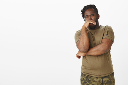 Disgusted unhappy dark-skinned man in military outfit, covering nose with palm from reek or awful smell, expressing dislike and antipathy from stink, standing displeased over gray background