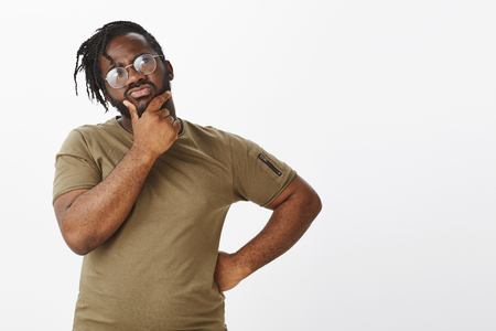 Hmm, what should guy do. Portrait of troubled focused handsome man with dark skin in t-shirt and glasses, holding hand on hip and rubbing chin while looking thoughtfully at upper right corner