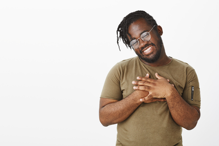 Studio shot of carefree african-american male model in glasses and casual clothes, holding palms on chest and tilting head with broad smile, being pleased or touched with warm compliments Stock Photo