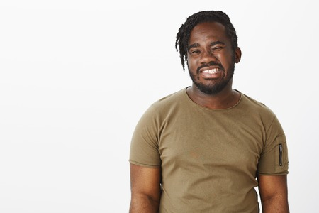Waist-up shot of positive happy african-american man with beard, winking and smiling broadly with perfect white teeth, feeling joyful while hanging out over gray background with cheerful attitude Stock Photo