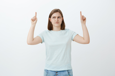 Girl have doubts think product is lame. Intense displeased cute girl with big ear frowning looking and pointing up with dislike and doubt hesitating if choice is right posing over white background Stock Photo