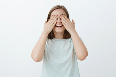Girl counting to ten ready to seek friends while playing hide-and-seek. Portrait of joyful and emotive cute woman in light-blue t-shirt waiting for surprise with closed eyes and palms on sight smiling